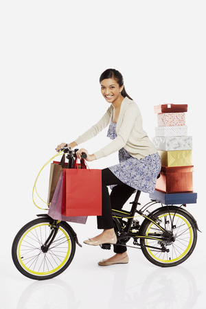 Woman riding a bicycle, carrying gift boxes and shopping bags photo
