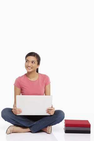 Woman using laptop while sitting on the floor