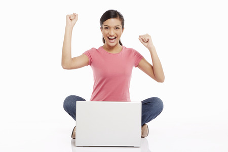 Woman using laptop and cheering photo