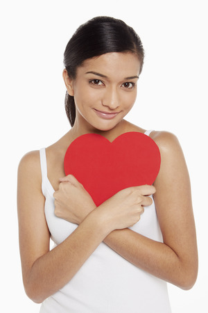 Woman holding a cut out heart shape photo