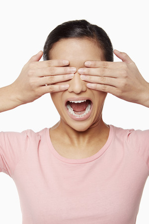 Woman using her hands to cover her eyes photo
