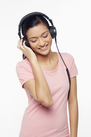 Woman listening to music through the headphone photo