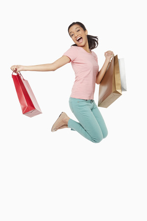 Woman carrying shopping bags, jumping mid air photo