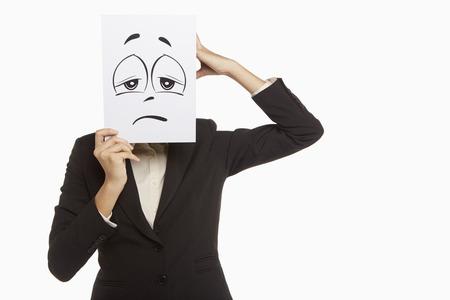 sad face: Businesswoman holding up a sad face doodle