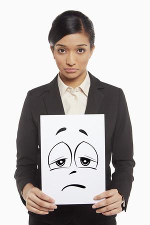 Businesswoman holding up a sad face doodle photo