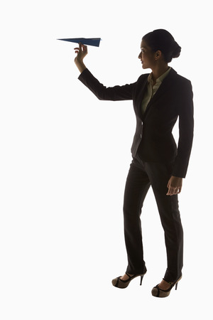 Businesswoman holding a paper airplane photo