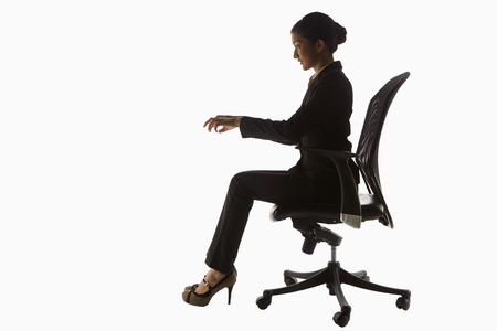 Businesswoman sitting on a chair, pretending to type photo