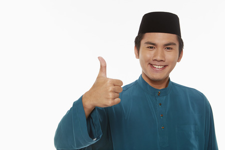 Man in traditional clothing giving thumbs up photo