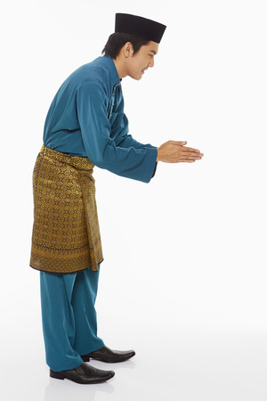 malay ethnicity: Man in traditional clothing showing hand greeting gesture