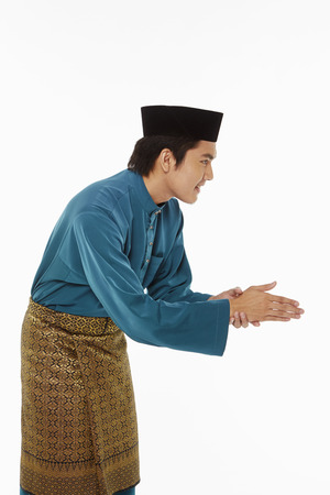 Man in traditional clothing showing hand greeting gesture