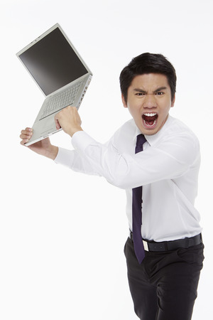 Angry businessman throwing a laptop