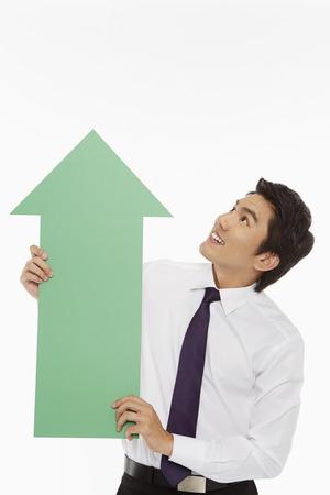 Businessman holding up a green arrow