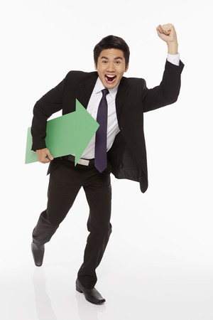 Businessman holding a green arrow and running photo