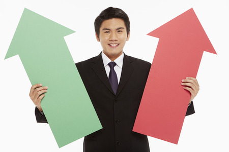 Businessman holding up a red and green arrow photo