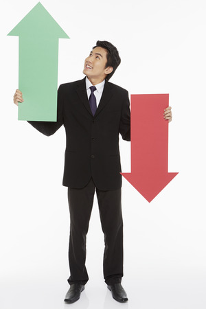 downwards: Businessman holding up a red and green arrow