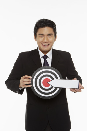Man holding up a dart board photo