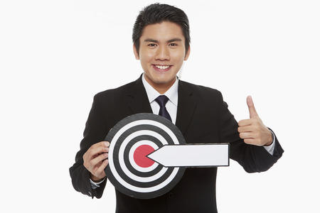 Man holding up a dart board, giving thumbs up photo