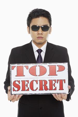 Man holding up a Top Secret sign photo