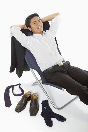 Businessman lying on a chair, smiling photo