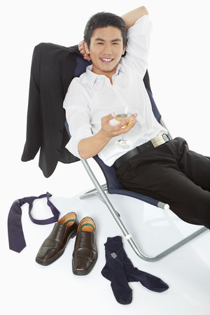 Businessman holding a drink while lying on a chair photo