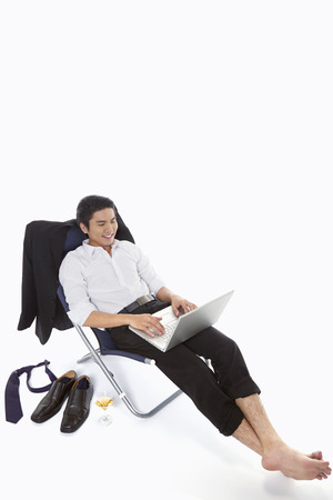Businessman using laptop while relaxing photo