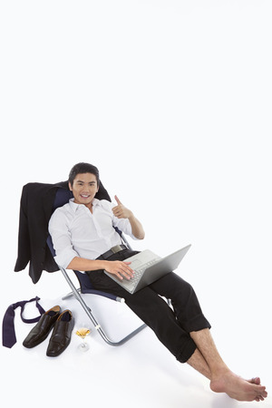 Businessman showing hand gesture while using laptop photo