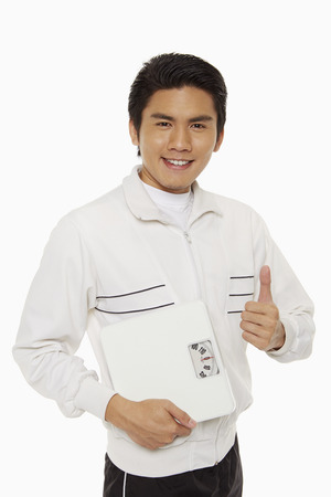 Man with weight scale giving thumbs up photo
