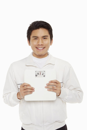 Man holding a weight scale and smiling photo