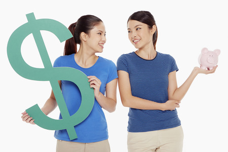 Women holding up a dollar sign and a piggy bank photo