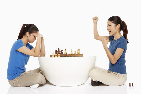 Woman cheering after winning a game of chess photo