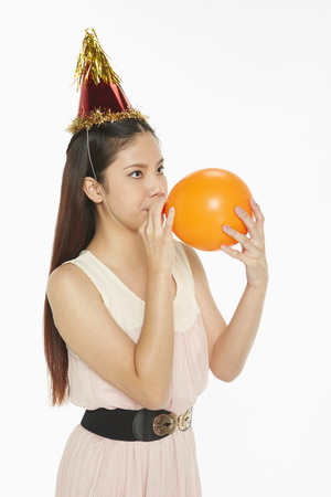 Woman blowing up a balloon photo