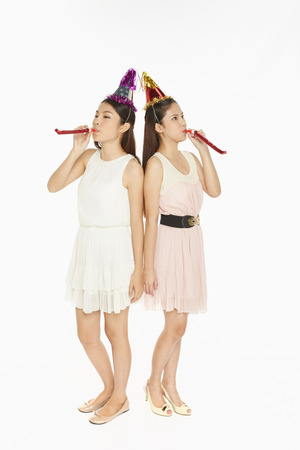 Two women blowing a party horn blower photo