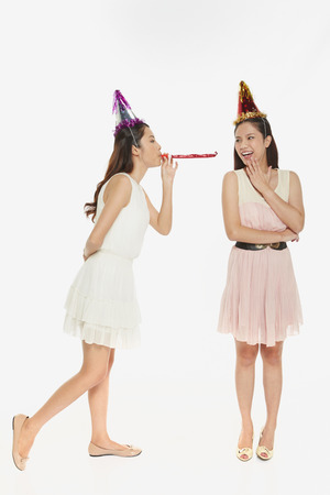 Woman blowing the party horn blower at her friend