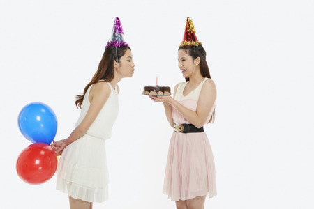 Woman blowing a candle on birthday cake photo