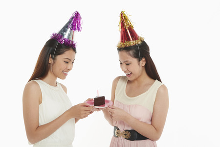 Women holding a plate with birthday cake on it photo