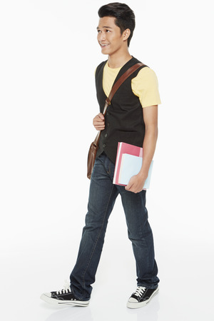 Man carrying books and a sling bag, smiling photo