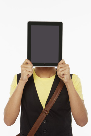 Man holding up a digital tablet, covering his face photo