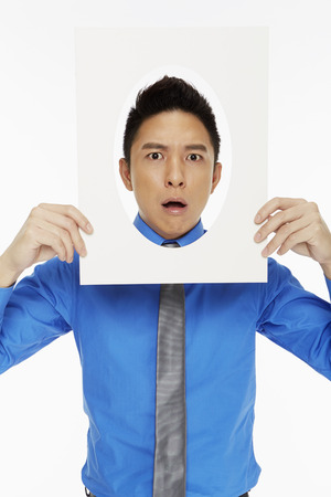 Businessman holding up an oval frame, gasping photo