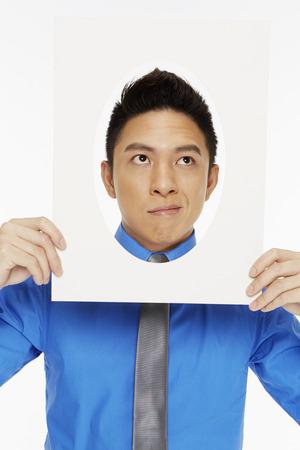 arrogancia: Hombre de negocios la celebraci?n de un marco ovalado, sonriendo Foto de archivo