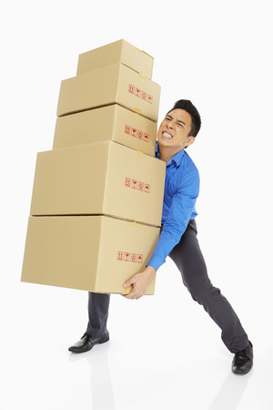 Businessman carrying a stack of cardboard boxes