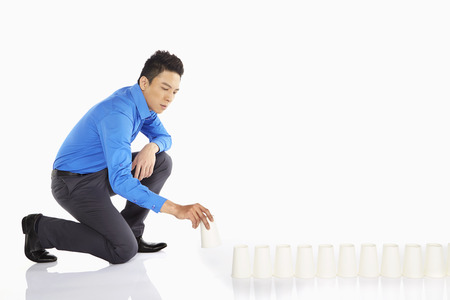 Businessman arranging disposable cups photo