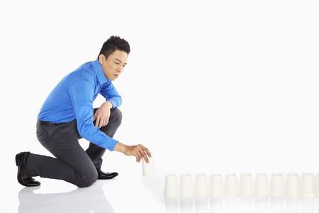 Businessman arranging disposable cups
