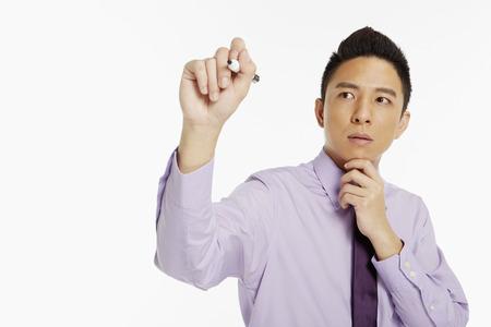 marker pen: Businessman holding up a marker pen, writing