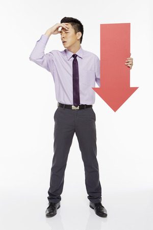 Businessman holding an arrow, pointing downwards