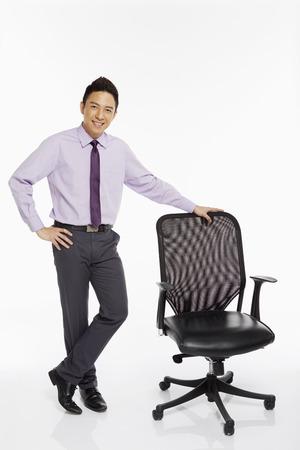 Businessman standing beside a chair