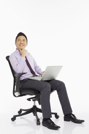 Businessman sitting on a chair and using laptop