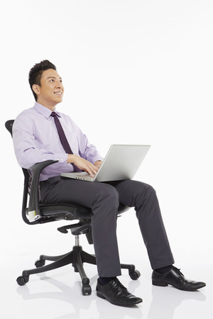 Businessman sitting on a chair and using laptop photo