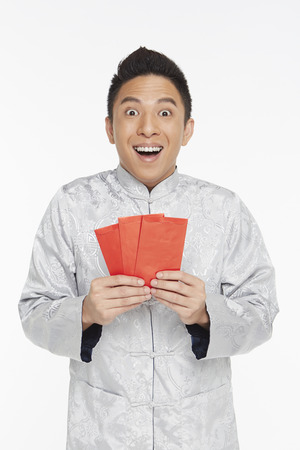 Man in traditional clothing holding up red packets photo