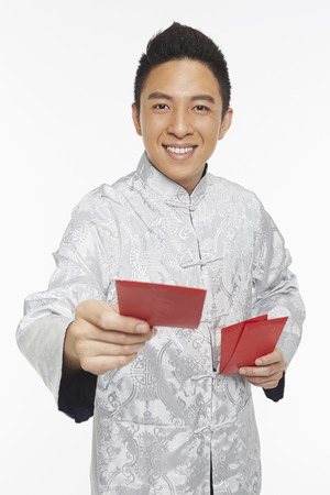 Man in traditional clothing handing out red packets Banco de Imagens