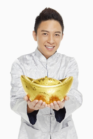 Man in traditional clothing holding a gold ingot photo